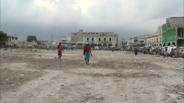 january 7 2011 pan survivors of the 2010 earthquake walking in devastated area with makeshift outdoor market lining the ruins of surrounding... - resourceful stock videos & royalty-free footage