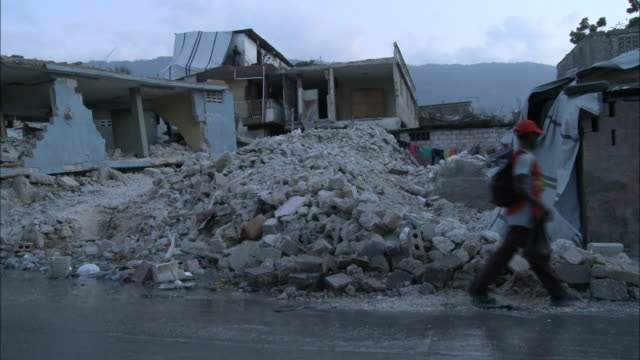 january 8 2011 pan light traffic and residents walking on the streets next to destroyed homes and rubble / portauprince haiti - haiti stock videos & royalty-free footage