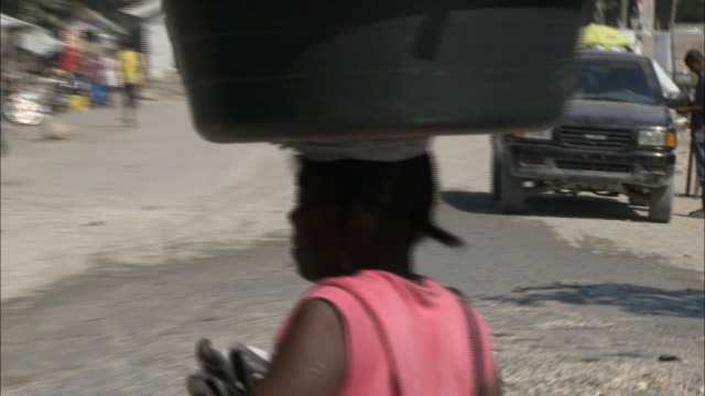 january 8 2011 ts local carrying her wares in a basket on her head while walking through a damaged village / leogane haiti - portare video stock e b–roll