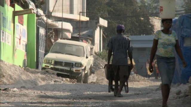 stockvideo's en b-roll-footage met january 8 2011 montage villagers carrying baskets on their heads pushing a wheelbarrow and walking down a narrow gravel lane in town / haiti - grind