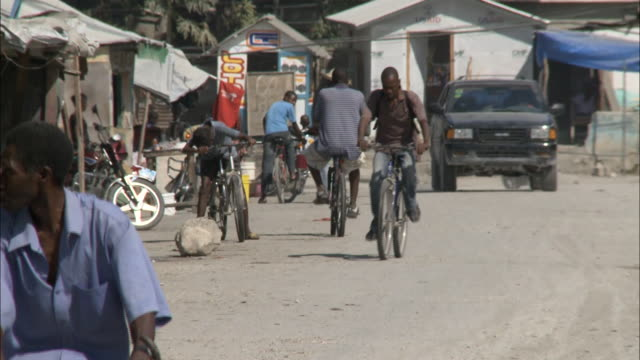 january 8 2011 pan pedestrians bicyclists and traffic and rubble along a dirt road in the village / leogane haiti - resourceful stock videos & royalty-free footage