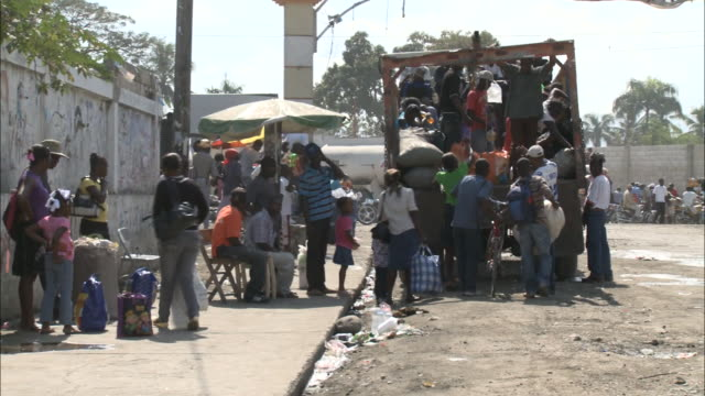 january 8, 2011 villagers loading goods into the back of a truck parked along a street with light traffic / leogane, haiti - 2010 video stock e b–roll