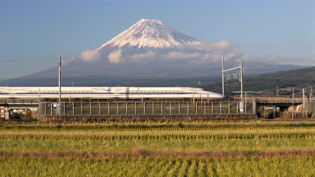 japan, honshu, mount fuji, shinkansen bullet train passing through harvested rice fields below the snow capped volcano - mt fuji stock videos & royalty-free footage