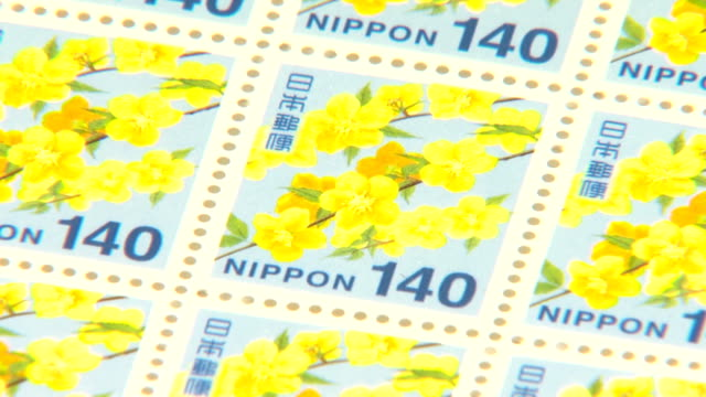 japan post co. has renewed the designs of 12 postal stamps to feature cherry blossom tree and other impressive natural motifs of the country, company... - mail点の映像素材/bロール