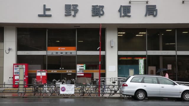 a japan post co mail pushes his bicycle while delivering mail in tokyo japan on tuesday sept 8 a japan post co mail carrier sorts mail while standing... - 郵便局点の映像素材/bロール