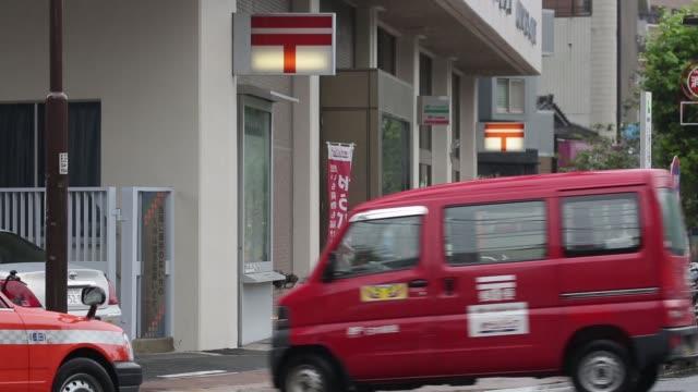 vídeos y material grabado en eventos de stock de japan post co vans sit parked as a japan post co van drives past in tokyo in tokyo japan on tuesday sept 8 a japan post co van stops at a traffic... - oficina de correos