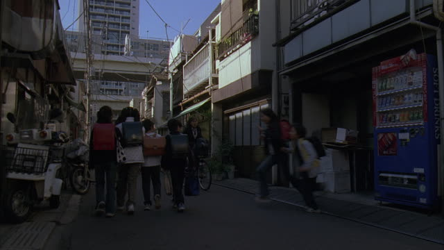ms, japan, tokyo, group of schoolchildren walking in narrow street, rear view - japanese school uniform stock videos & royalty-free footage
