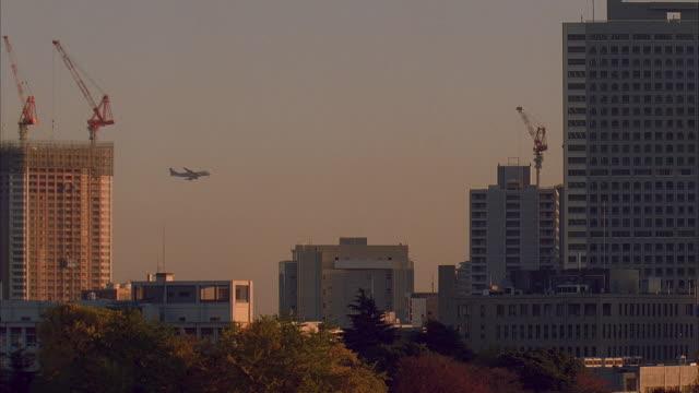 ws, japan, tokyo, passenger jet flying over buildings - 2005年点の映像素材/bロール