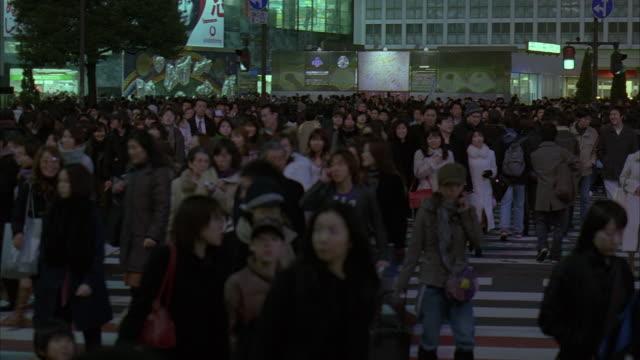 ms, pan, japan, tokyo, shibuya ward, pedestrians crossing street decorated for christmas, dusk - 2005年点の映像素材/bロール