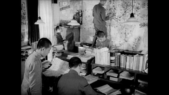 Japanese administration building car leaving gates INT WS Propaganda office workers CU Anticommunists poster Nazi Swastika sign MS Japanese man at...