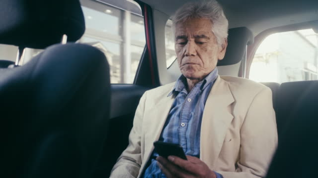 Japanese adult senior man riding in taxi and using smart phone