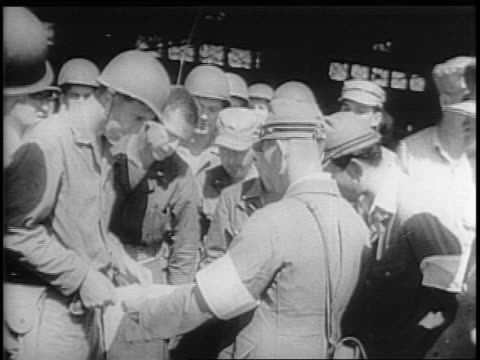 japanese and american troops look at a large paper / soldiers salute as the us flag is raised at yokosuka naval base / japanese vice admiral... - japanese surrender stock videos and b-roll footage