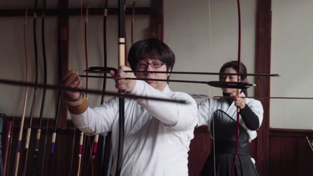 vidéos et rushes de archer japonais prépare son arc - terme sportif