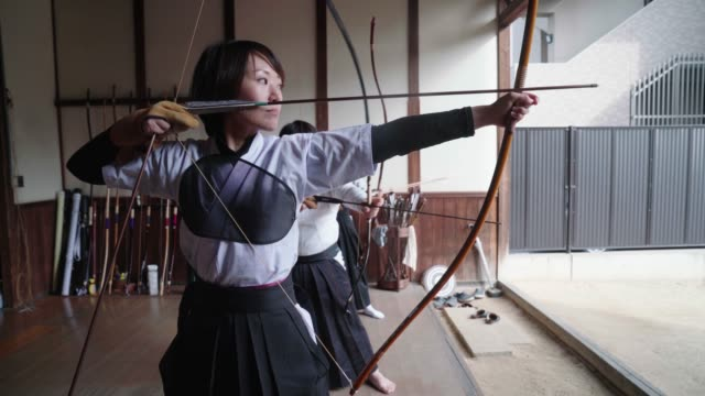 vídeos de stock e filmes b-roll de japanese archer readying her bow and taking her shot - authority