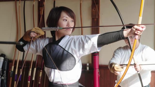 日本の射手は、aim を取り、彼女の矢を解放 - 権力点の映像素材/bロール