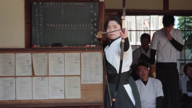 japanese archer takes aim and releases her arrow - mid adult men stock videos & royalty-free footage