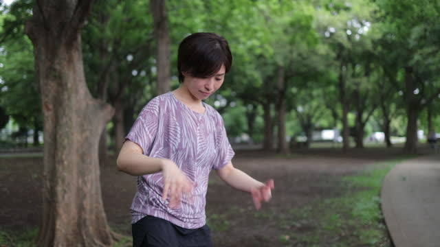 japanese athlete warming up in public park - warm up exercise stock videos & royalty-free footage
