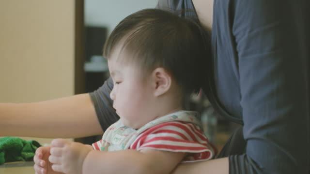 vídeos de stock, filmes e b-roll de japonês bebê comendo comida de bebê com uma colher. - comida de bebê