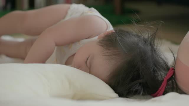 日本の赤ちゃんは彼女の睡眠中寝返り。 - 床点の映像素材/bロール