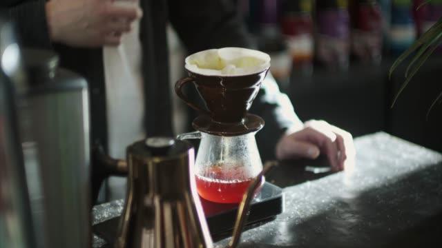 接地されているコーヒーを飲みながらお湯を注いで日本バリスタ - 入れる点の映像素材/bロール