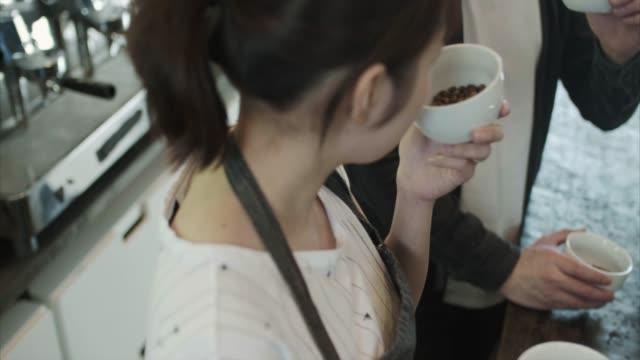Japanese barista smells fresh coffee
