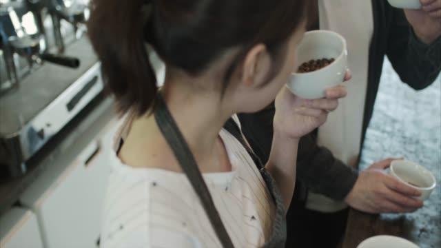 Japanese barista smells fresh coffee  (slow motion)