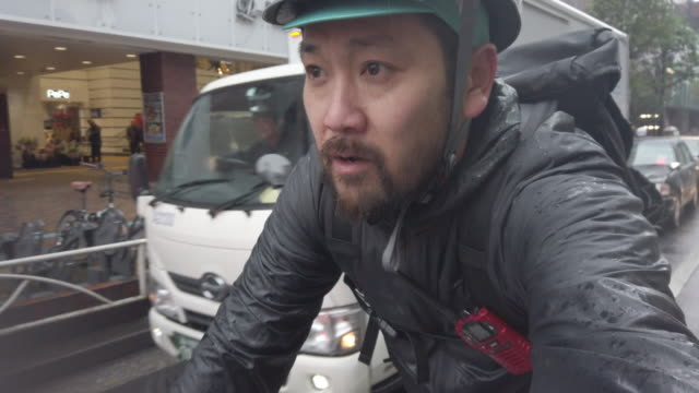 japanese bike messenger riding in rainy tokyo - part time worker stock videos & royalty-free footage