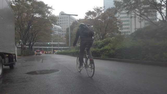 japanese bike messenger riding in rainy tokyo - helmet stock videos & royalty-free footage