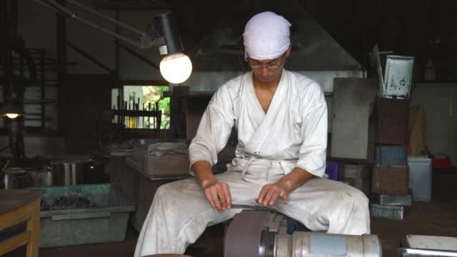 Japanese blacksmith sharpening a blade in his workshop