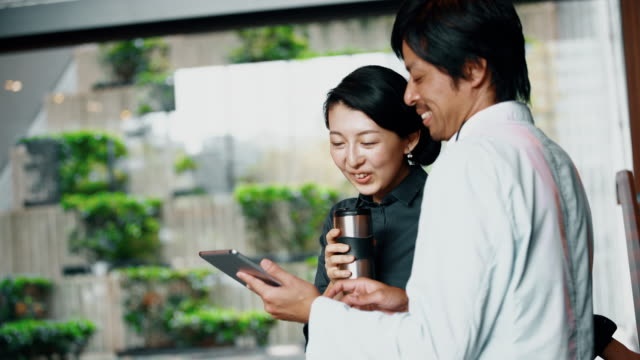 ms japanese business colleagues using a digital tablet - lobby stock videos & royalty-free footage