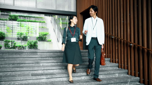 ds japanese business couple walking down the stairs - lobby stock videos & royalty-free footage