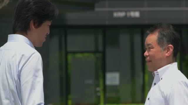 vídeos de stock, filmes e b-roll de homem de negócios japonês falando ao ar livre. - vestuário de trabalho formal
