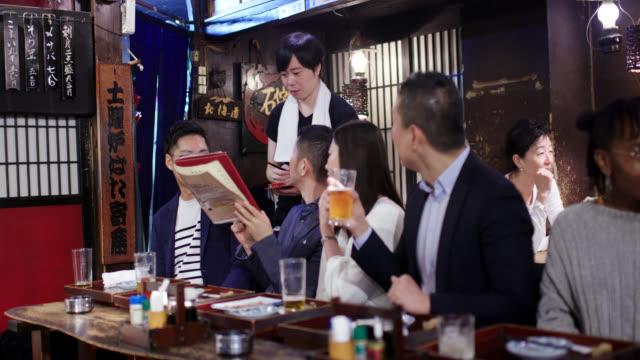 居酒屋での仕事の後に食べ物を注文する日本のビジネスマン - 注文する点の映像素材/bロール