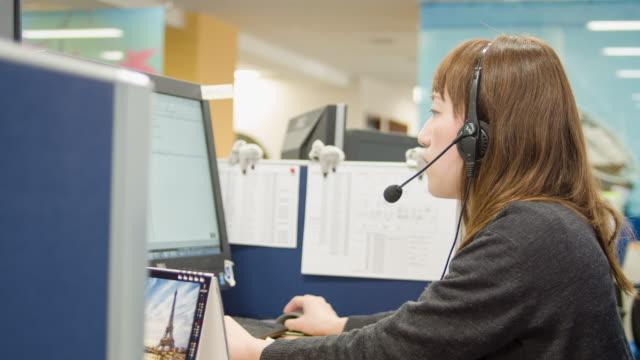 vídeos y material grabado en eventos de stock de japanese business person talking on headset in office. - desk