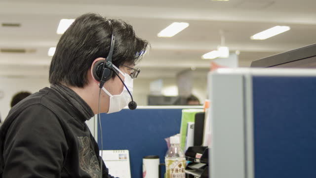 Japanese business person wearing mask working in office.