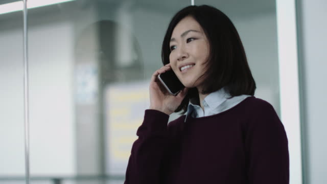 Japanese business woman in office talking on phone