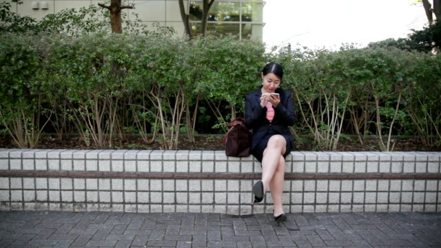 japanese business woman uses smart phone - cross legged stock videos & royalty-free footage
