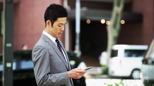 japanese businessman checking phone - portability点の映像素材/bロール