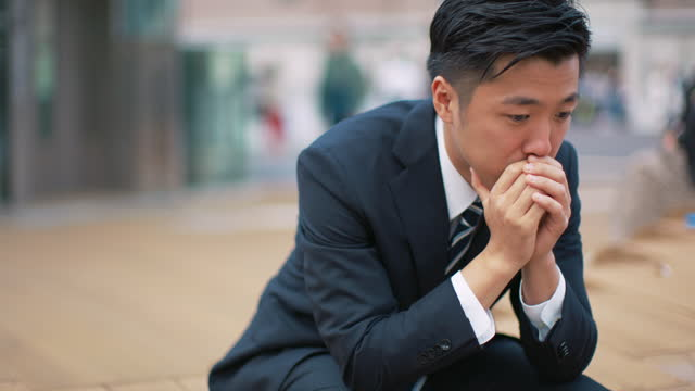 a japanese businessman holds his head in his hands - loneliness stock videos & royalty-free footage