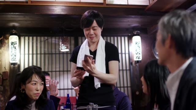 居酒屋で夕食を払う日本のビジネスマン - 居酒屋点の映像素材/bロール