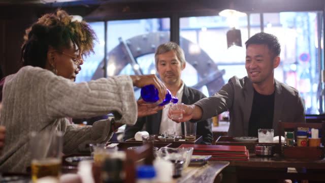 日本人居酒屋で観光客に日本酒を注ぐ日本のビジネスマン - 居酒屋点の映像素材/bロール