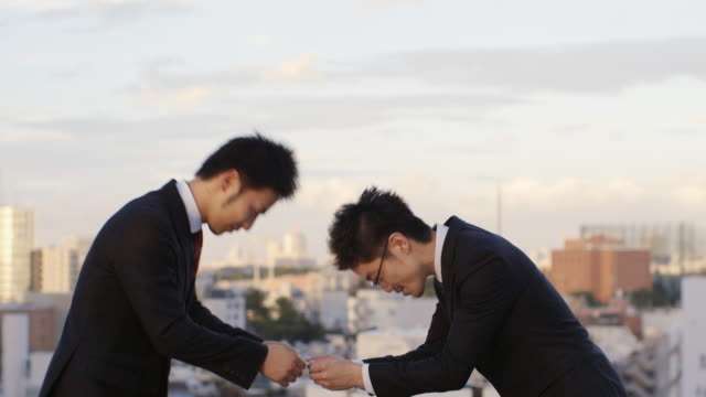 ms a japanese businessman presents his business card and bows / tokyo, japan - マナー点の映像素材/bロール