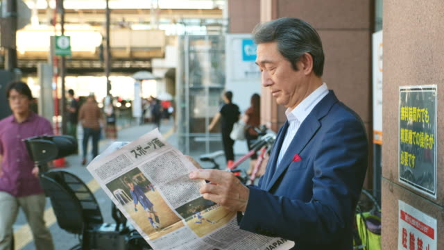 vídeos de stock e filmes b-roll de japanese businessman reading newspaper - jornal