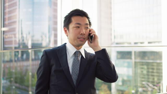 ms a japanese businessman talks on a mobile phone in an office / tokyo, japan - ホワイトカラー点の映像素材/bロール