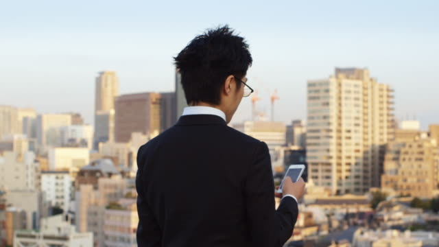 ds, ms japanese businessman types on his phone on tokyo rooftop / tokyo, japan - スーツ点の映像素材/bロール