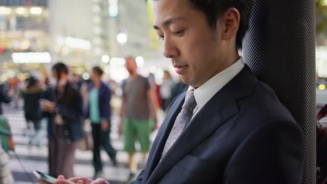 CU A Japanese businessman using a mobile phone at Shibuya crossing / Tokyo, Japan