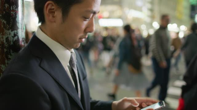 vidéos et rushes de cu a japanese businessman using a mobile phone at shibuya crossing / tokyo, japan - east asian ethnicity