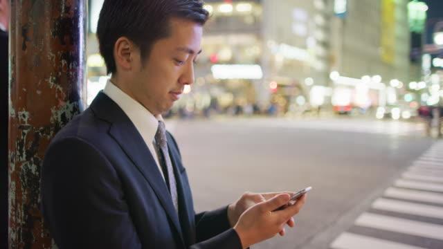 ms a japanese businessman using a mobile phone at shibuya crossing / tokyo, japan - 横顔点の映像素材/bロール