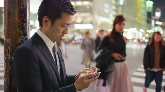 ms a japanese businessman using a mobile phone at shibuya crossing / tokyo, japan - 待つ点の映像素材/bロール