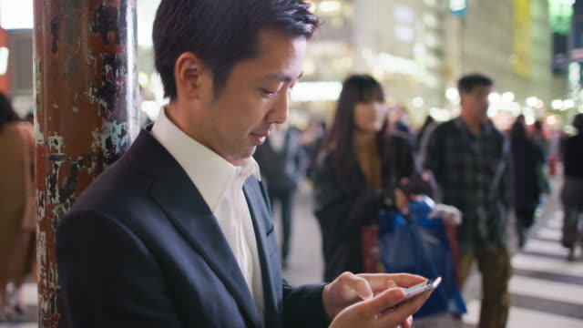 cu a japanese businessman using a mobile phone at shibuya crossing / tokyo, japan - asia stock videos & royalty-free footage